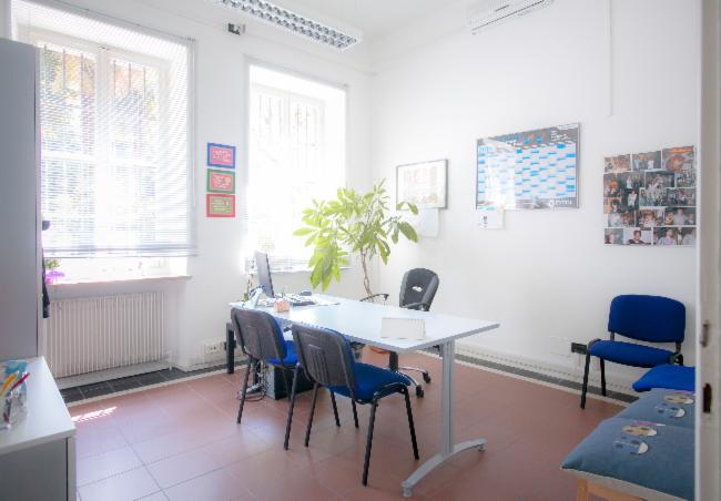 un ufficio con una scrivania con sopra un monitor e delle sedie blu