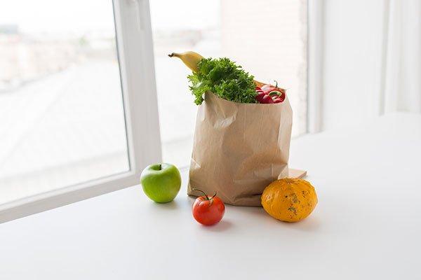 Frutta e vegetali all'interno di un sacchetto di carta accanto a una finestra