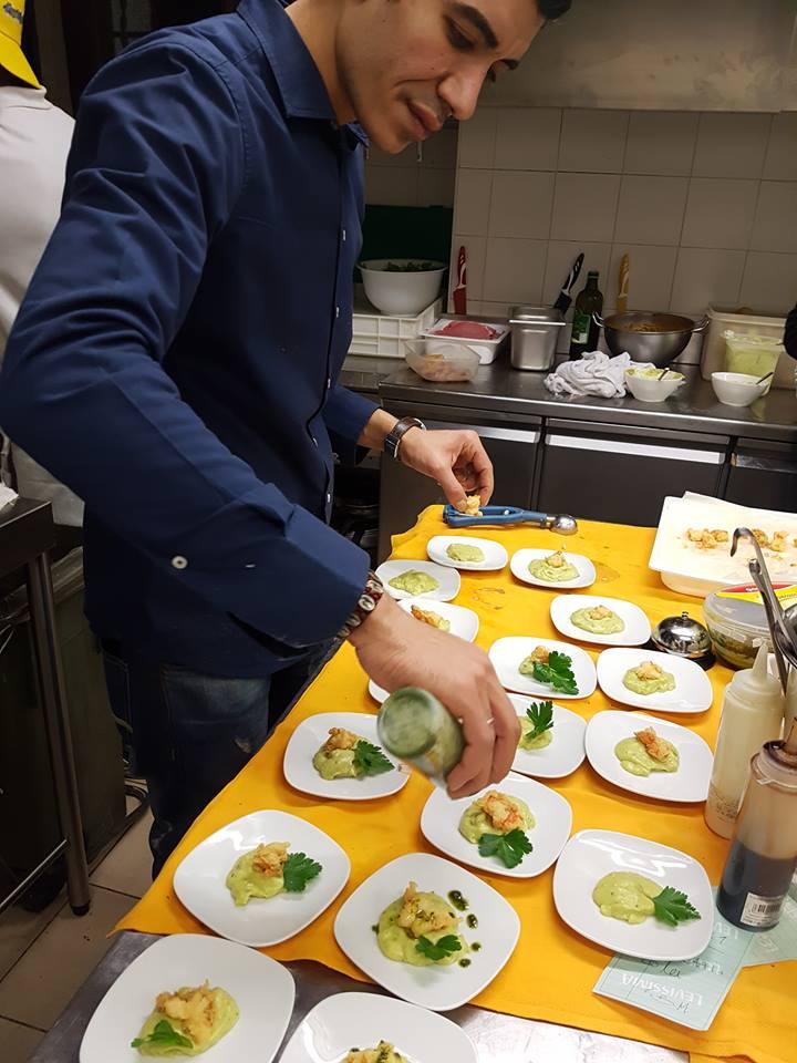 addetto alla cucina che condisce antipasti con una salsa verde