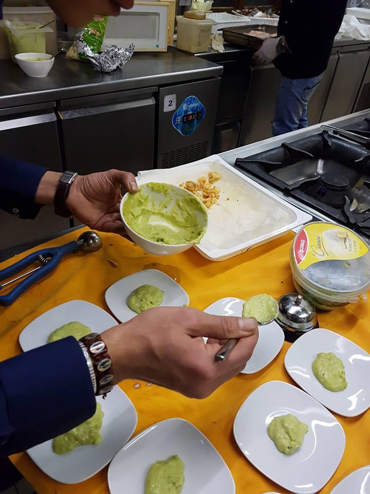 Dettaglio di un assistente alla cucina che prepara piatti con una salsa verde