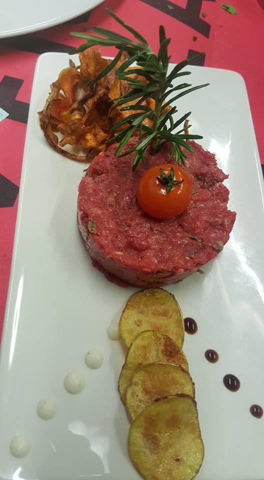 Tartare di carne guarnita con pomodorini e patate