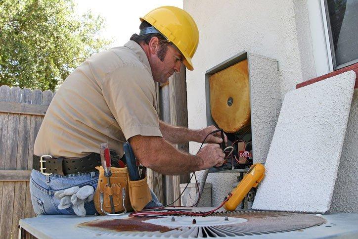 repair man working on ac unit