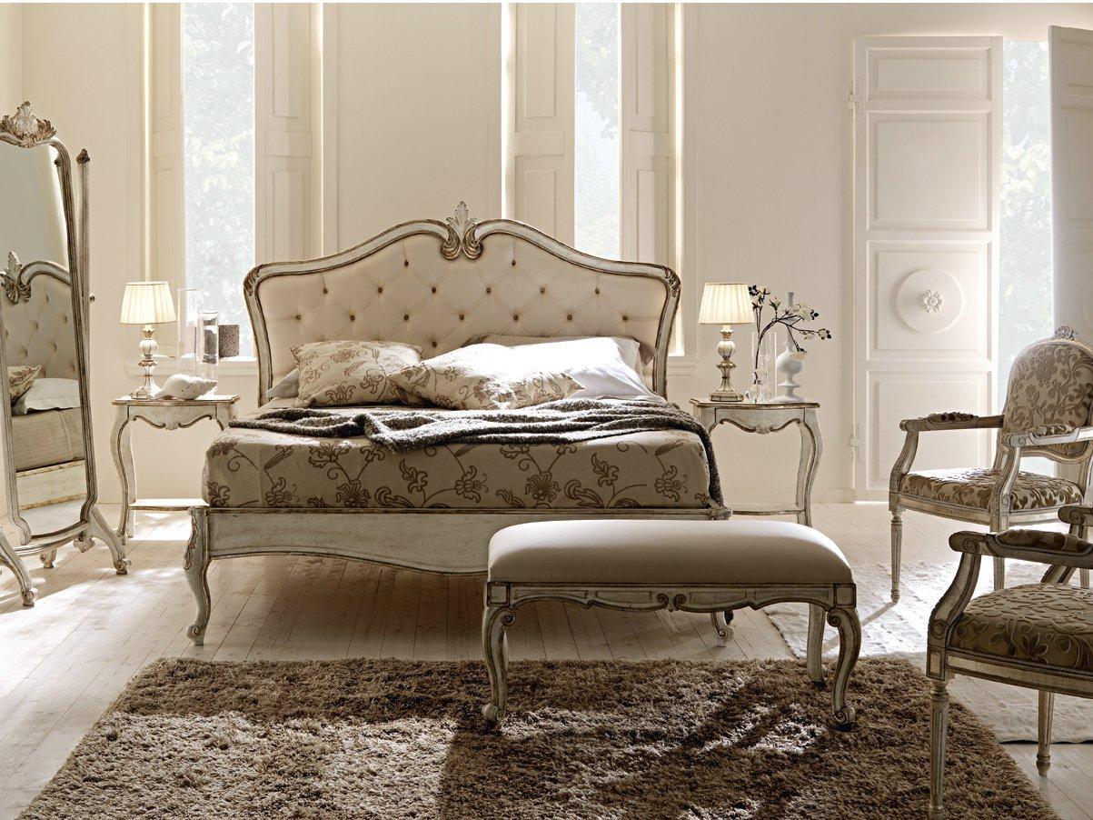 Camera da letto con uno sgabello, un tappeto e un letto con due mobiletti e due lampade