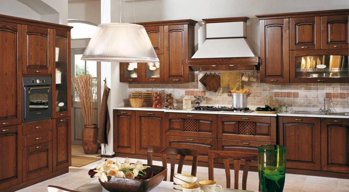 Cucina classica tutta in legno con un tavolo, due sedie e due lampadari