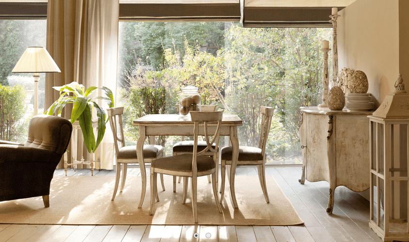 Cucina con tavolo, quattro sedie, delle piante e una vetrata