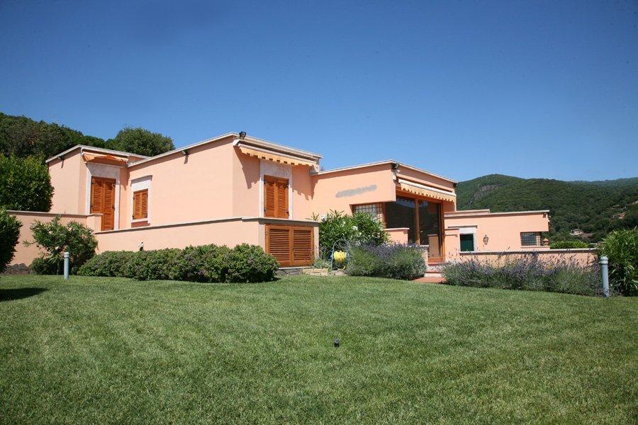 vista frontale di una casa indipendente con muro color rosa chiaro