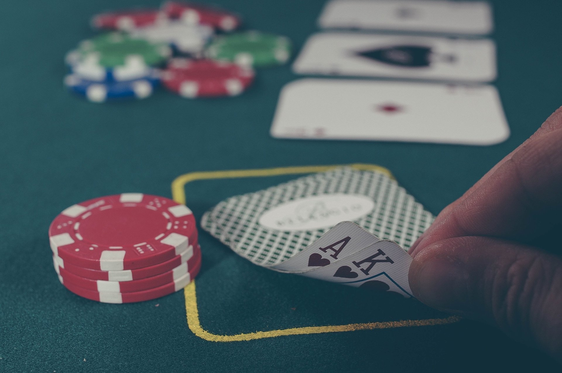 cards and chips on a gambling table and man needing counselling for gambling addiction
