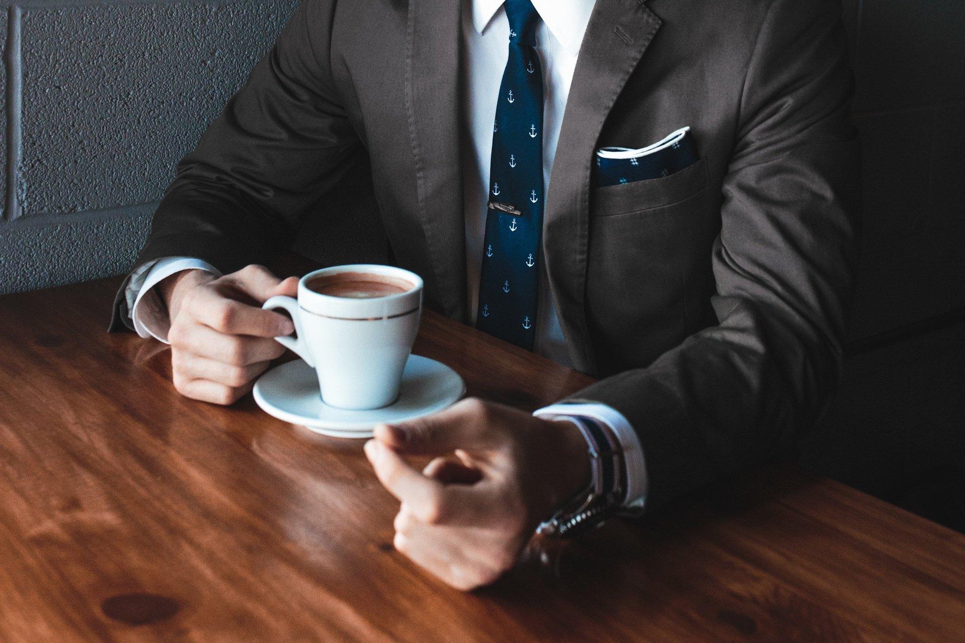Caffettiera, tazza di caffè e piatto di pastini