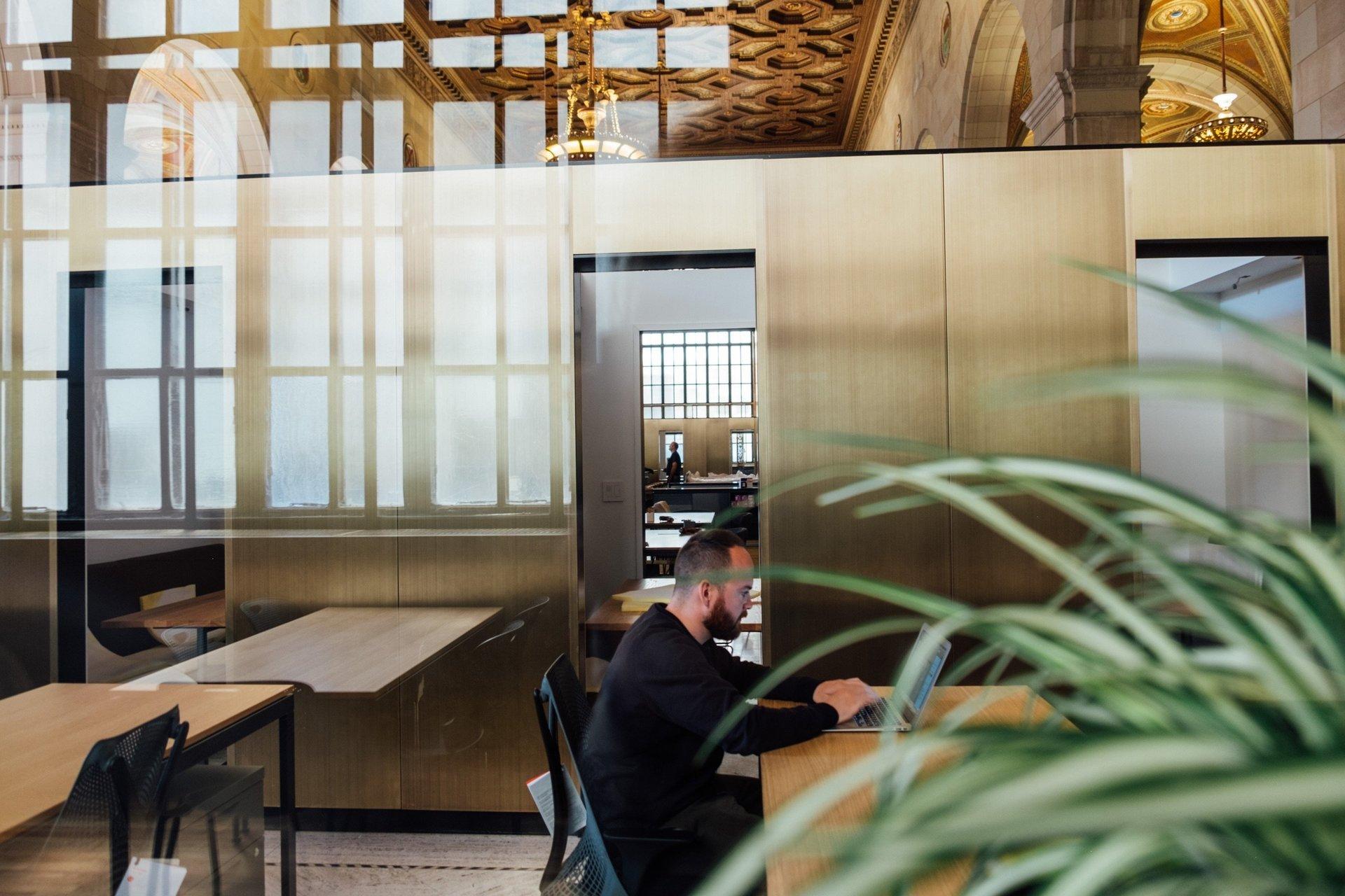 uomo seduto alla scrivania in open space di un ufficio